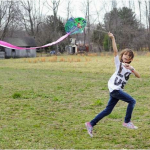 Tori Higbee,7, a second-grader, runs to get her kite in the air.