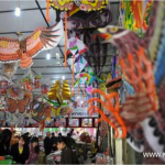 Tourists gather to purchase kites in a kite store in Weifang, east China's Shandong Province, April 18, 2011. Photo: Xinhua