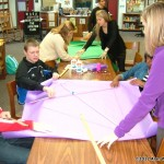 Mrs. Kemp's students working away adding the bulletin board paper to the kite frame.