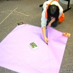 Tenth grader Diana Tran draws out her kite frame so that she can cut out her kite sail.