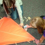 L/R  Ninth graders Taylor Bruce and Bronte Rapps find that clothes pens are useful for holding down the edges of the kite so that the glue will dry.  More fun than hanging clothes!