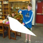 Ninth grader Brady Gantt demonstrates the 45 degree kite angle needed to tie the overhand knot on the bridal in order to attach the line.
