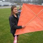 Ninth grader Emily Heimberger stands ready with her team's kite.  The kite tails are made of torn up tee shirts provided by our athletic department's Coach Michael Quinn.  Thanks coach Quinn.  The old tees added a lot of color to our kites.  Ninth grader Brittany Wheeler and some other student helpers tied up the kite tails for the kites.  Thanks girls for all the help.