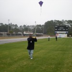 Junior Larshaun Sessions runs with purple kite gaining altitude with each stride and smiling all the way.  Kites often cause kite fliers to smile and shout with excitement.  Scientists are still trying to find out what causes this behavior in people.  Someone tell the scientists that flying kites is fun!