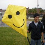 Yo bani Rafaella hold his team's smiley kite.  I didn't know that kites smiled but now I think they do.