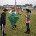 L/R  Ninth grader Blake Marsh, twelth grader Kaitlin Sweeney and ninth grader Kareena Patel take a break from flying their kite high.  They were excited flying their prehistoric kite.